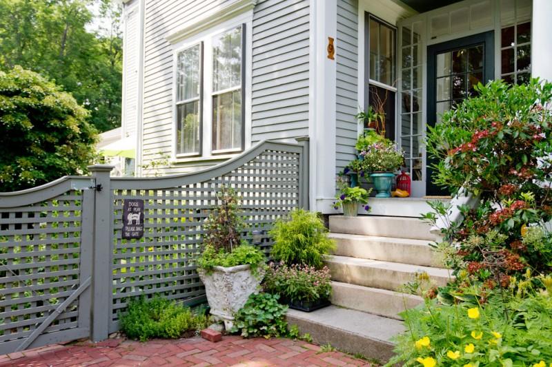 lattice fence design brick pavers stairs windows garden plants lanterns pots windows traditional design