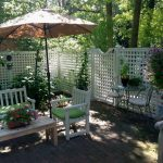 lattice fence designs chairs tables glass top table sunbrella flowers plants trees traditional patio outdoor area