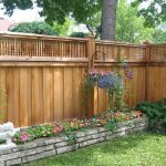 lattice fence designs low stone walls garden flowers hanging pots cherub statue transitional design