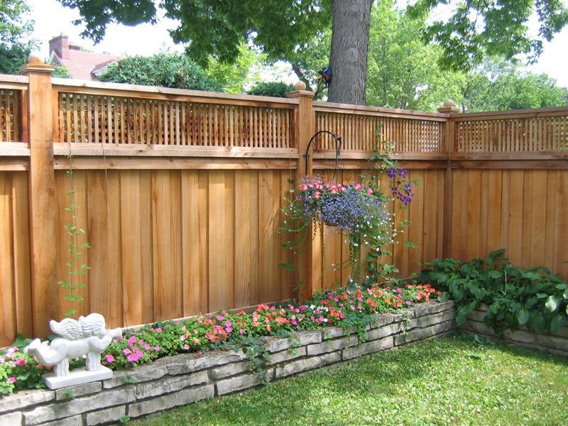 lattice fence designs low stone walls garden flowers hanging pots cherub statue transitional design