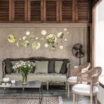 living room with brown wall, grey floor tiles, vintage sofa with grey cushion, long coffee table, white wooden rattan chairs