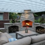 mid sized classic backyard patio design with a fire feature a pergola and natural stone pavers rattan framed sofa with beige color