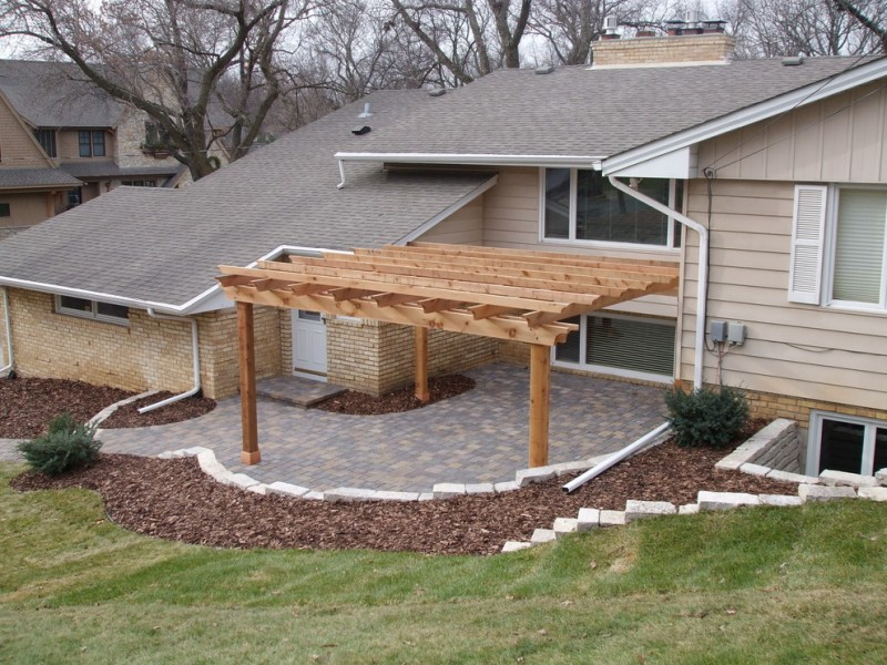 mid sized pergola built from cedar natural stone paving floors red bricks exterior walls wooden slabs exterior walls