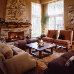 Mission Styled Living Room With Stone Finished Fireplace A Couple Of Brown Chairs A Pair Of Dark Brown Ottomans Light Beige Couch With Grey Accent Pillows Dark Brown Couch With Decorative Pillows