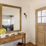 modern entryway table door sconces mirror flower vase tray hardwood floors white walls traditional design