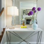 modern entryway table hardwood floors rugs lamp mirror staircase ceramic vase books transitional design