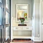 modern entryway table mirror hardwood floors carpet drawers double doors vase transitional design
