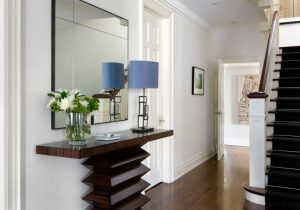 modern entryway table stairs railing hardwood floors lamp mirror glass vase door framed painting transitional design