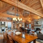 Mountain Home Floor Plans Rusting Dining Table Set Grey Couches Wood Flooring And Ceiling Fireplace And Stones Mantel Rustic Chandelier Open Kitchen Area Gray And White Rugs