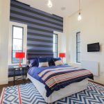 Multicolored Bedding Treatment Multicolored Area Rug Blue Black Stripes Wall Painting White Walls A Pair Of Red Table Lamps
