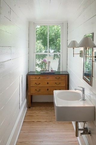 narrow bathroom antique & mission styled chest with dark marble top clean white walls wall mounted sink in white metal framed mirror medium toned wood floors