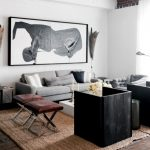 nate berkus furniture coffee table leather ottomans grey sofa standing lamp sidetable rug hardwood floors artworks beach style