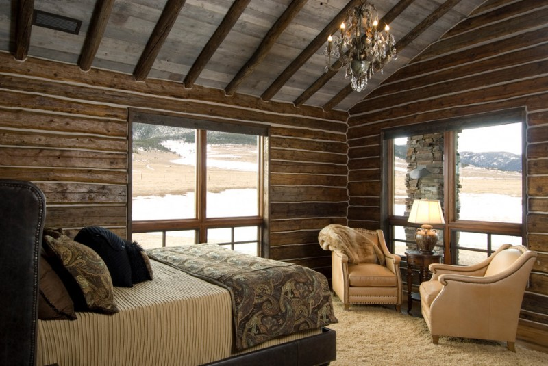 one bedroom cabin plans plank walls bed couches round table lamp chandelier bedding carpet hardwood floors oversized windows rustic design