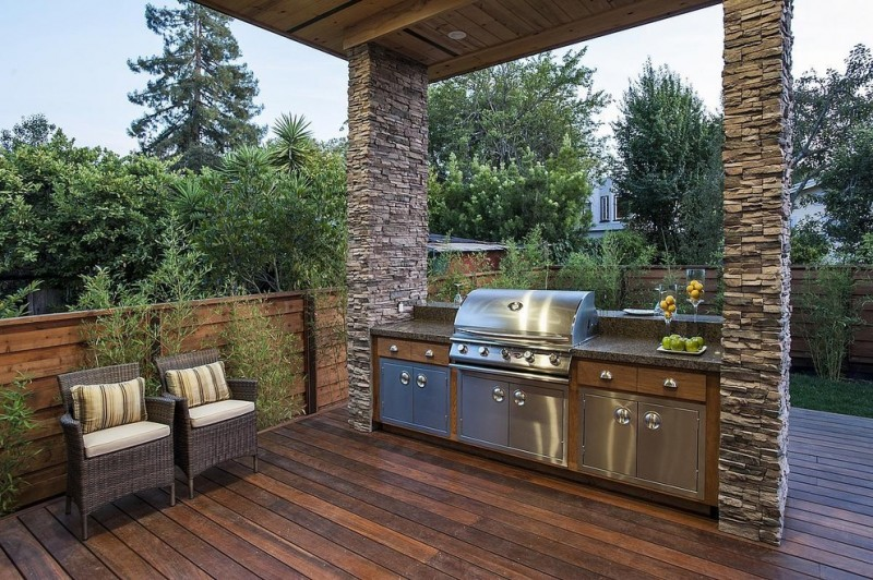 outside kitchen design wood floor chairs stone pillars plants traditional porch