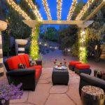 Patio With Black Rattan Chairs With Red Cushion, Matching Tables And Ottomans Under A Pergola With Light Strands Twisted