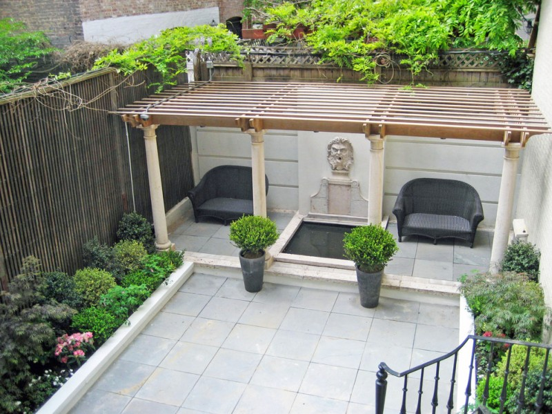 patio with wood pergola bluestone floors large concrete edged planters and a couple of loveseat