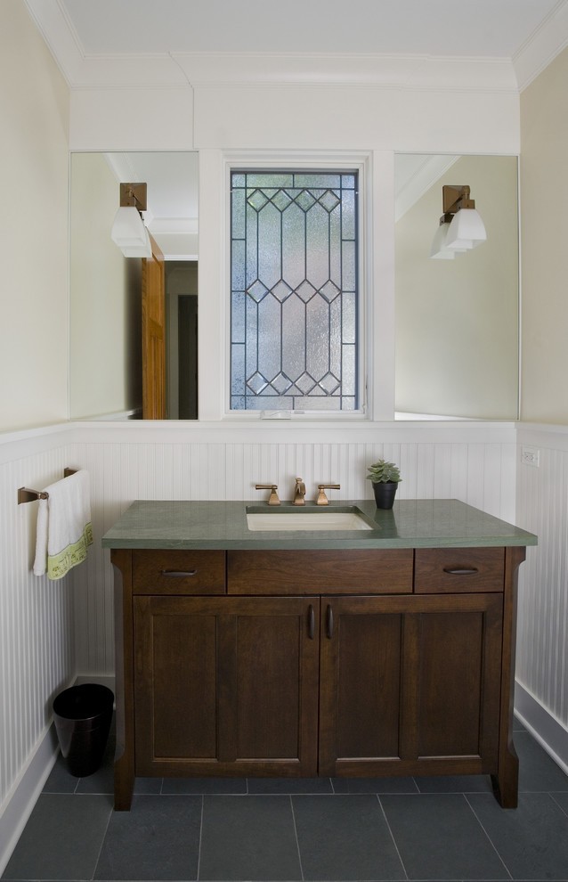 powder room with Mission Style vanity dark wood vanity with cabinet dark green countertop undermount sink white wainscoting and decorative glass window