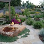 rock fire pit wooden swing sloped garden grass trees colorful flowers flagstone walkway white flowers purple flowers pink flowers