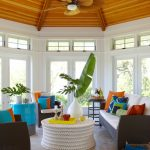 round sunroom with petal ceiling fan, dark rattan sofa with white cushion, blue orange pillows, white round table