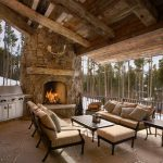 rustic corner stone fireplace wooden framed brown sofa wooden coffee table antler silver appliances cemented floor