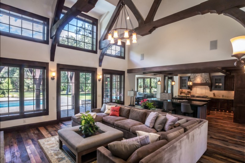rustic living room with sectional sofa pillows wood floor beautiful chandelier table flowers windows chairs lamps