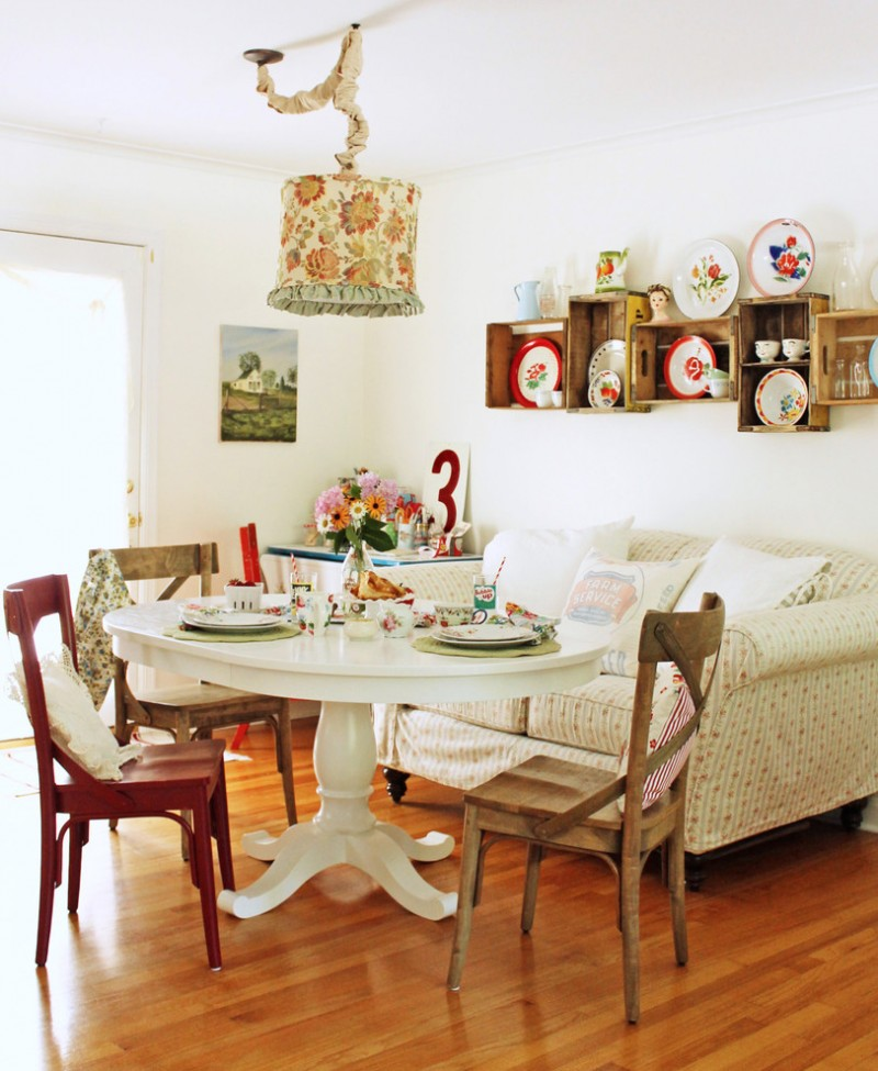 shabby dining room with flowery covered pendant lamp, wooden wall mounted shelves, white love seat, white wooden table, wooden chairs