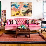 Shabby Living Room With Pink Sofa With Flowery Vintage Pillows, Brown Leather Ottoman, Colorful Striped Rug, Abtract Painting, Wooden Colorful Side Table