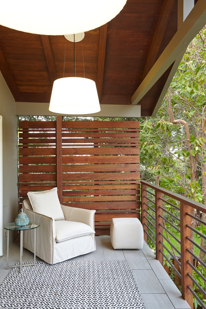 small balcony with wood rail, high wood slat on one side, grey tiles, white chair with ottoman, glass top side table