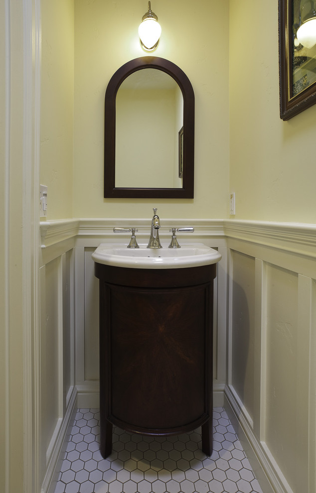 small powder room design dark wood cabinet white drop in sink dark wood framed mirror white painted wainscoting white hexagon tiles floors