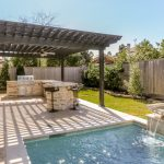 Solid Grey Pergola Light & Neutral Stone Pavers Floors Natural Stone Outdoor Kitchen Idea Outdoor Pool With Waterfall Feature