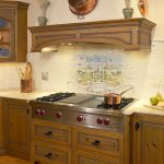 spanish tile backsplash wolf gas rangetop saucepan with lit wood flooring wooden kitchen cabinet nice hood cover