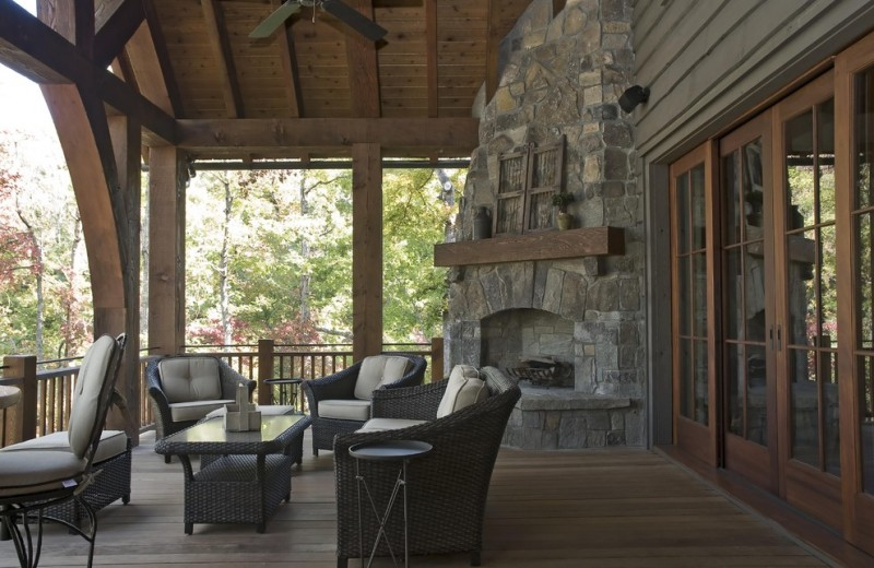 stone outdoor corner fireplace black rattan chair sets wooden deck floor ceiling wooden framed glass door