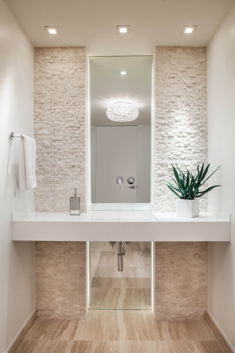 stone wall floating vanity built in sink pendant light recessed lights tiled wooden floor floor to ceiling mirror flower arrangement