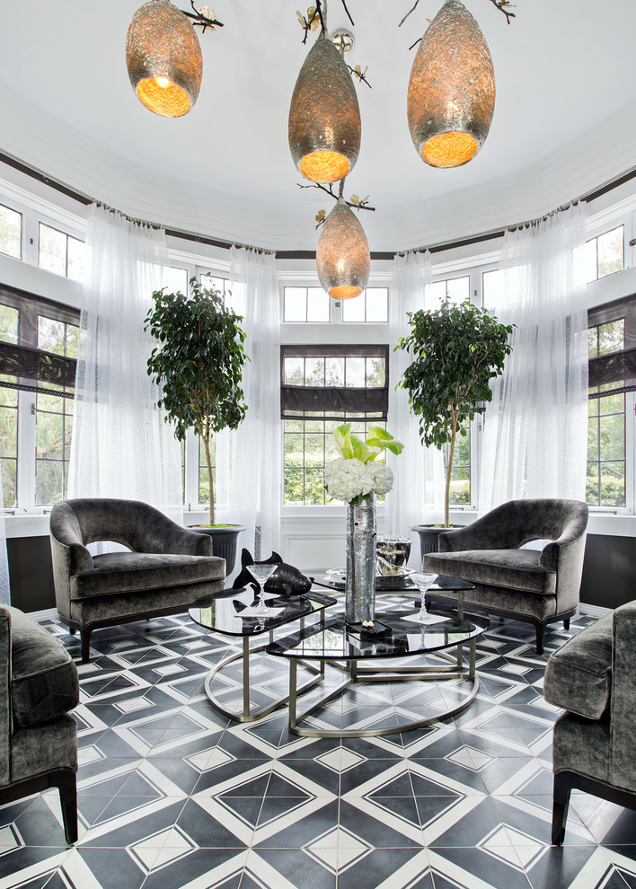 sunroom with grey couches, dark glass coffee tables, silver high flower vase, white see through curtain, plants, white and black floor