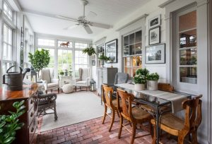 sunroom with white chair with high back, white wooden side table, grey rattan chair, grey rug, rattan ottoman, hanging fan, dining area nearby
