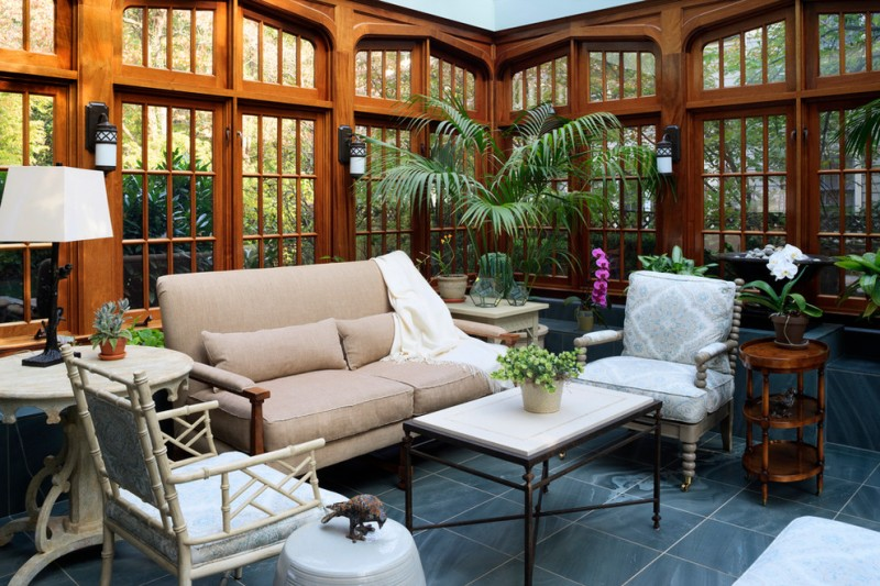 sunroom with wooden traditional window, brown sofa, rattan chairs with white cushion, white wooden chairs, white coffee table, white wooden side table, white table lamp, g