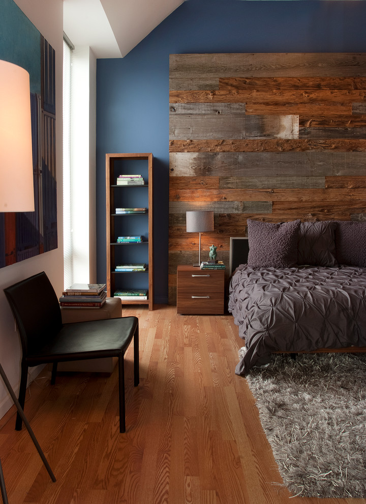 textured grey bedding treatment medium toned wood floors blue walls accented by shabby wood board reclaimed wood furniture grey fury area rug