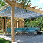 Traditional Backyard Patio Idea With Oak Pergola Oak Partitions L Shape Blue Couch With Decorative Pillows Black Side Table Blue Rectractable Canopy Paver Floorings