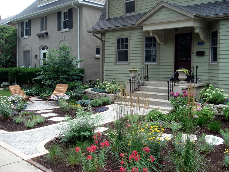 traditional front yard landscape with steppingstone path and perennial flower beds wooden door with glass and glass window deck wooden wall