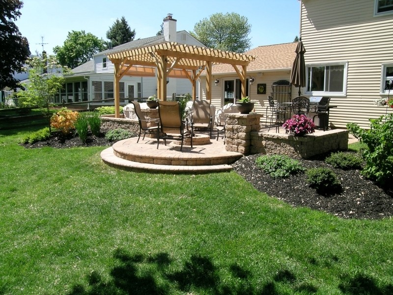traditional patio with wood perloga without finishing a set of exterior furniture stone made sitting walls stone floors outdoor lighting fixture