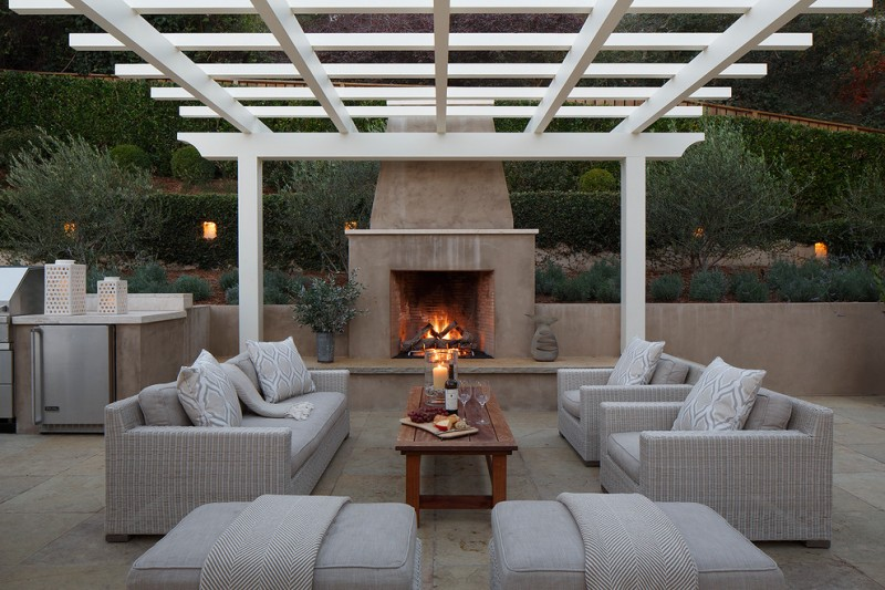 transitional backyard patio idea with clean white pergola stucco finished walls and floors light grey couches with pillows wooden center table