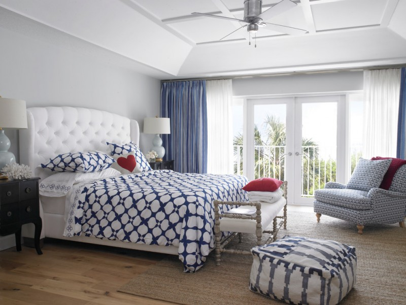 transitional bedroom with cotton bedding in white & navy blue blue draperies knitted armchair in soft blue pale toned wood floors pale toned area rug