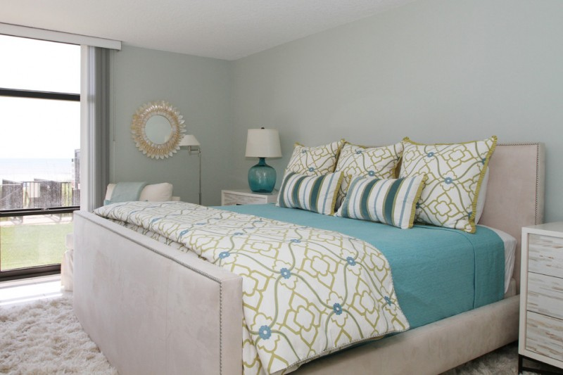 tropical bedroom idea Eastern accent comforter and shams blue bed skirt white bed frame flufy white area rug light blue walls