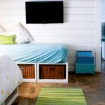 under the bed storage baskets beds pillows wall tv white walls beach style bedroom