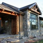 vacation home rustic exterior stone brick wall wooden deck wall stone brick patio glass window wooden door