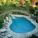 waterfalls for pools iron fence iron pool chairs and glass table curved swimming pool small waterfall artistic stone floor large umbrella