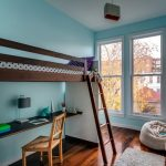 wooden framed loft bed wooden table and chair medium toned wooden floor blue wall paint glass framed windows