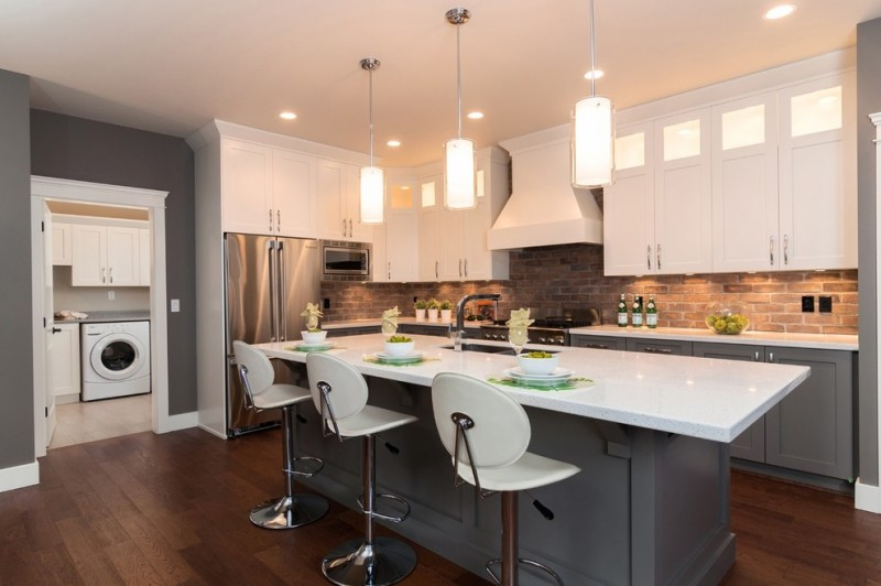 Contemporary kitchen with stainless steel appliances, blue lower cabinets, snowy white floating cabinets, brick backsplash medium toned wooden floors island bar stools