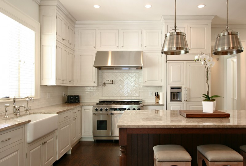 Elegant l shaped kitchen with a farmhouse sink, paneled appliances, raised panel cabinets, white cabinets, marble countertops, white backsplash and subway tile backsplash