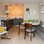 L Shaped Dining Bench Two Small Dining Chairs Round Shape And White Top Dining Table Pale Toned Wood Floors Grey Kitchen With White Ceranic Subway Tiles Backsplash